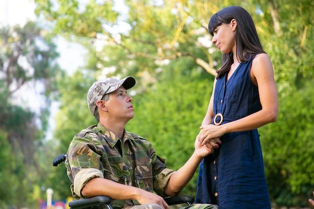 잠겨있는 여자와 휠체어 회의 및 야외 공원에서 이야기에 장애인 된 군사 남자. 장애인 베테랑 또는 관계 개념
