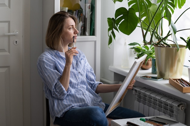 Задумчивая женщина-художник рисует картину на холсте, задумчиво смотрит в окно за вдохновением