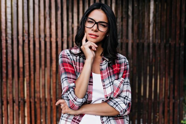 Donna pensierosa in camicia a scacchi che tocca la sua guancia. colpo esterno della ragazza latina in posa con l'espressione del viso sospettoso.