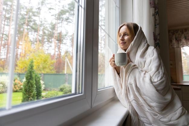 Задумчивая женщина пьет горячий травяной чай дома, думая, глядя в окно осенне-осенний сезон