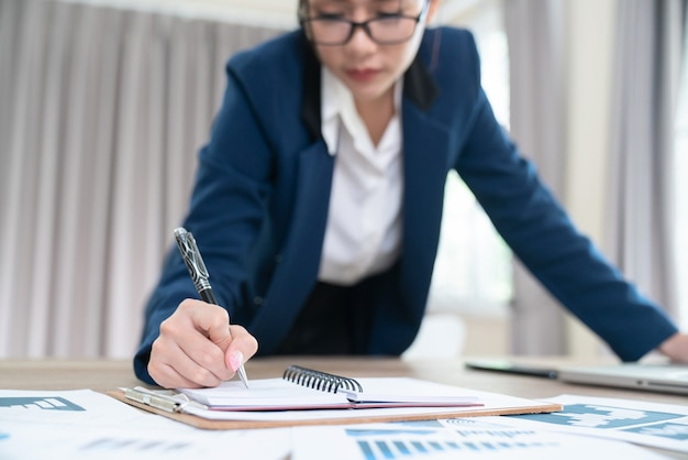 Pensive woman in eyewear planning working schedule writing in notebook while sitting