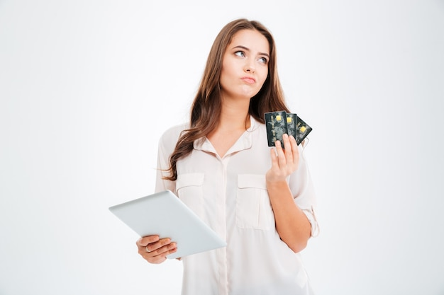 Pensive woman holding credit card and using tablet computer isolated on a white wall