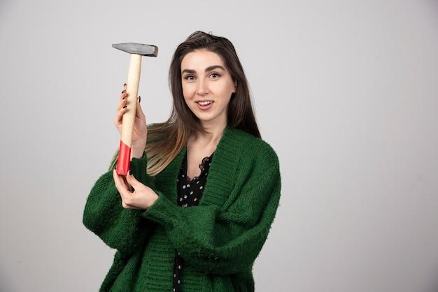 Donna pensierosa che tiene il martello in mano su uno sfondo grigio.