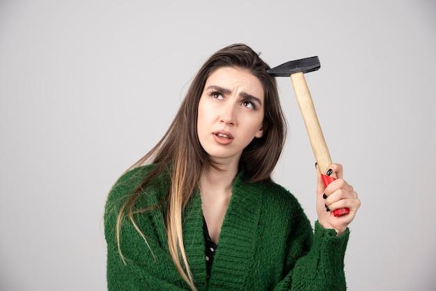 Задумчивая женщина, держащая молоток в руках на сером фоне.