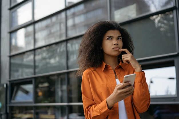 Pensive woman holding smartphone, shopping online.  beautiful african american girl waiting for taxi