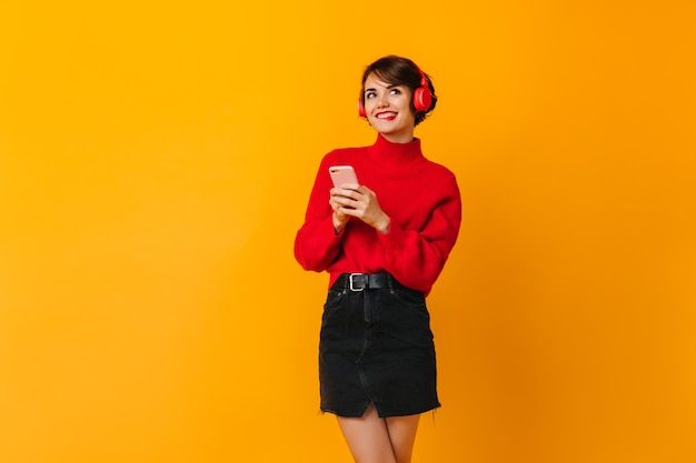 Задумчивая женщина в черной юбке держит смартфон