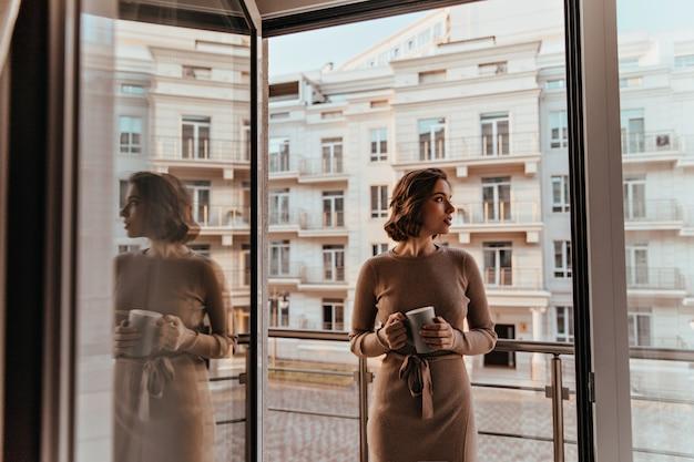 カプチーノを飲む茶色のドレスの物思いにふける女性。バルコニーの近くに立っているコーヒーのカップを持つ素晴らしいハンサムな女の子の肖像画。