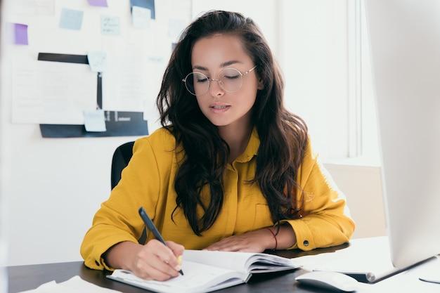 작업 장소에 앉아있는 동안 노트북에 쓰는 작업 일정을 계획하는 안경에 잠겨있는 여자