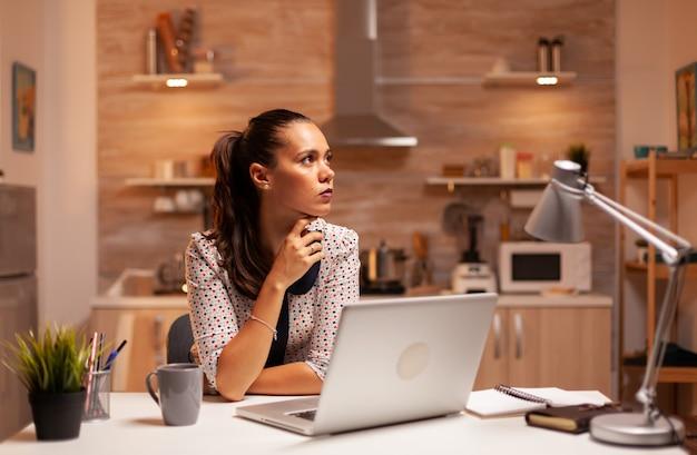 夜遅くにラップトップで作業している間、家庭の台所で物思いにふける女性。深夜に最新のテクノロジーを使用して、仕事、ビジネス、忙しい、キャリア、ネットワーク、ライフスタイル、ワイヤレスで残業している従業員。