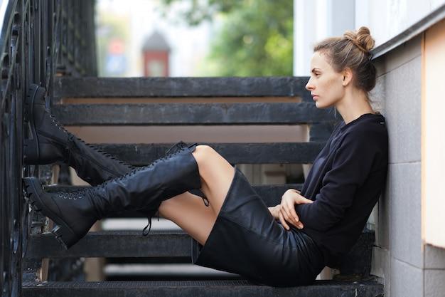 革のスカートと階段に座っているラフなレースアップブーツで物思いにふける女性