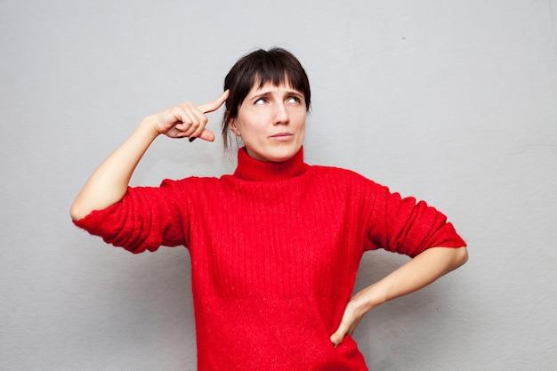 赤いセーターを着た物思いにふける女性は、灰色の壁の額にスティックを立てかけました
