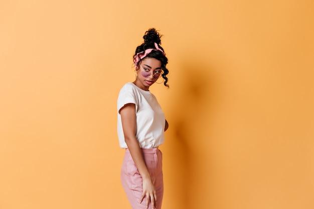 黄色の壁に立っているサングラスの物思いにふける女性