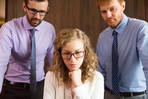 Pensieroso donna guardando in basso con due uomini dietro
