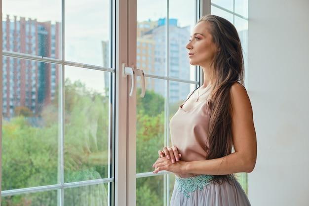 Задумчивая женщина смотрит в окно дома