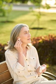 Pensive woman putting on wireless earphone