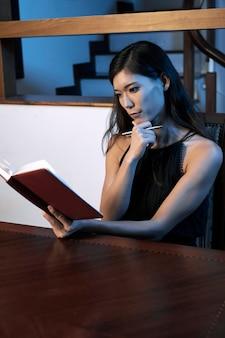 Pensive woman reading diary