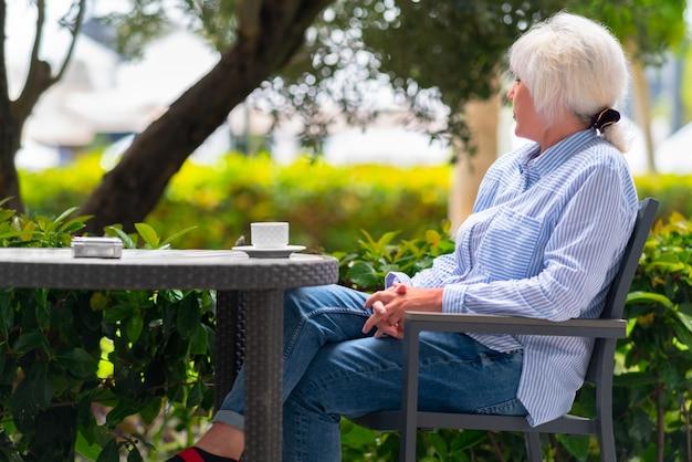 レストランのテーブルの屋外パティオでくつろぐ物思いにふける女性