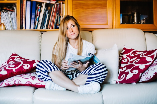 Pensive woman relaxing with magazine