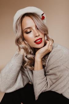 Donna pensierosa in berretto alla moda che si siede sulla parete marrone
