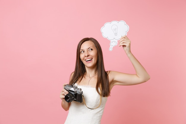 Pensive woman in white dress hold retro vintage photo camera, say cloud speech bubble with lightbulb choosing staff, photographer
