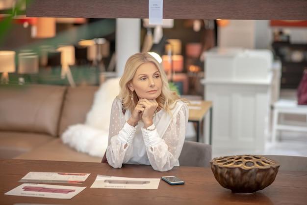 Мечтательная женщина с светлыми волосами, сидя за столом в мебельном магазине, серьезное мышление.