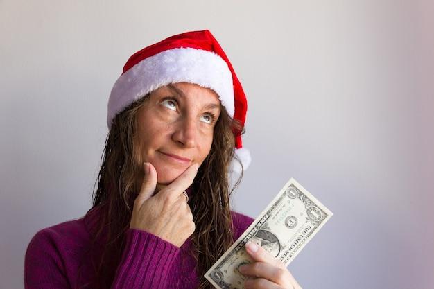 흰색 배경 위에 1달러 지폐를 들고 크리스마스 빨간 모자와 잠겨있는 여자
