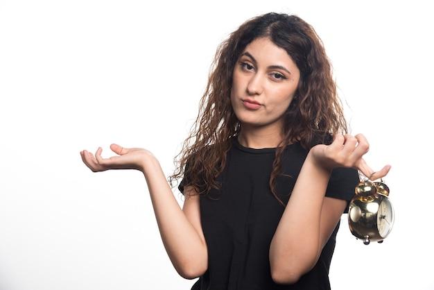 Una donna pensierosa con un orologio in mano su sfondo bianco. foto di alta qualità