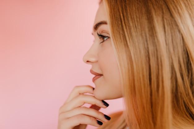 ピンクの上に立っている長いまつげを持つ物思いにふける女性。まっすぐな髪型の寒さで満足している白人女性