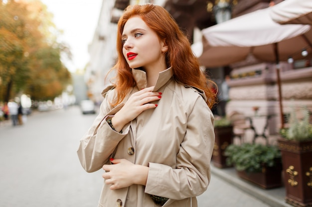 Pensive woman with red hairs and bright make up walking on the street. wearing beige coat and green dress.