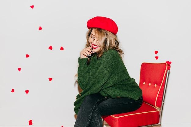 Задумчивая женщина с блестящими волосами сидит на красном стуле и улыбается