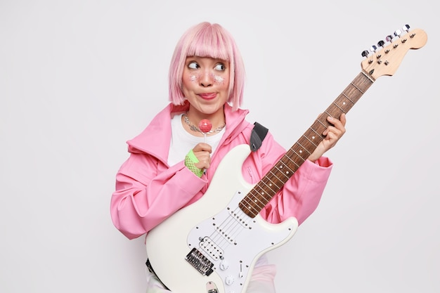 Pensive woman with trendy pink hairstyle licks lips holds sweet lollipop poses indoor holds acoustic bass electric guitar dressed in stylish outfit
