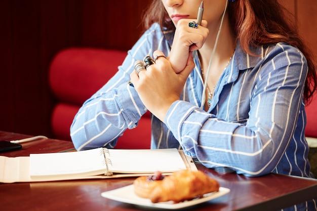 Задумчивая женщина, работающая в кафе