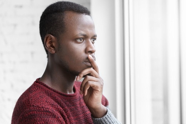 Pensive worried african american art director dressed casually keeping finger on lips