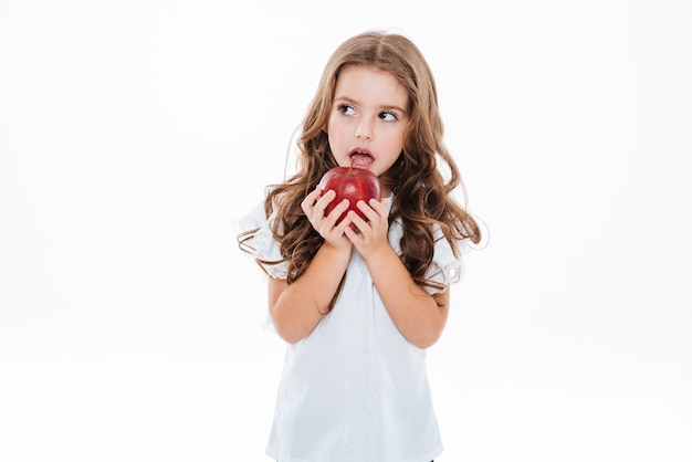 物思いにふける心配して立っている小さな女の子と赤いリンゴを保持
