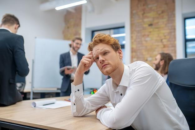 꿈꾸는 테이블에 앉아 잠겨있는 젊은 성인 redhaired 남자와 사무실에서 뒤에 얘기하는 동료