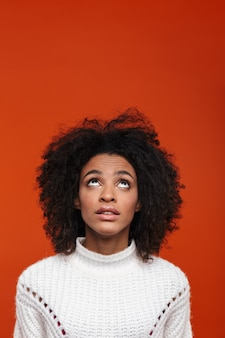 Pensive young african woman wearing casual clothes standing isolated over red wall, looking up
