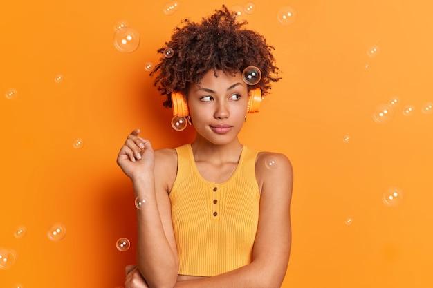 La giovane donna afroamericana pensierosa concentrata da parte ascolta musica tramite cuffie stereo ha un'espressione premurosa vestita in abiti casual gode di una canzone di testi isolata sopra la parete arancione