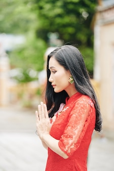 Задумчивая молодая азиатская женщина в красном платье молится на открытом воздухе, cocenpt духовности и религии