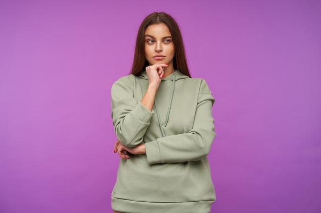 Pensive young attractive brown haired woman squinting her eyes while looking thoughtfully aside and holding her chin with raised hand, isolated over purple wall