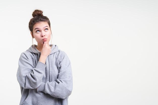 Задумчивая молодая привлекательная брюнетка женщина с повседневной прической, держащая подбородок с поднятой рукой, задумчиво глядя вверх, изолированные на белом фоне