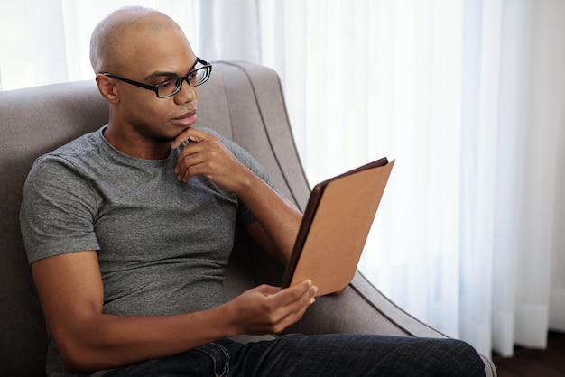 Pensive young bald black man in glasses sitting in armchair and reading intresting book on tablet computer
