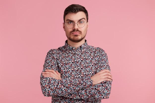 Pensieroso giovane maschio barbuto con gli occhiali in camicia colorata pensando a qualcosa, in piedi con le mani incrociate un sopracciglio sollevato interrogatorio, con un'espressione seria e perplessa sul muro rosa