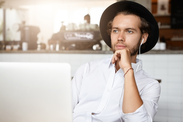Pensive young bearded man wearing white shirt and black hat touching his chin and looking ahead of him with faint smile, using laptop to listen to his favorite music online in earphones