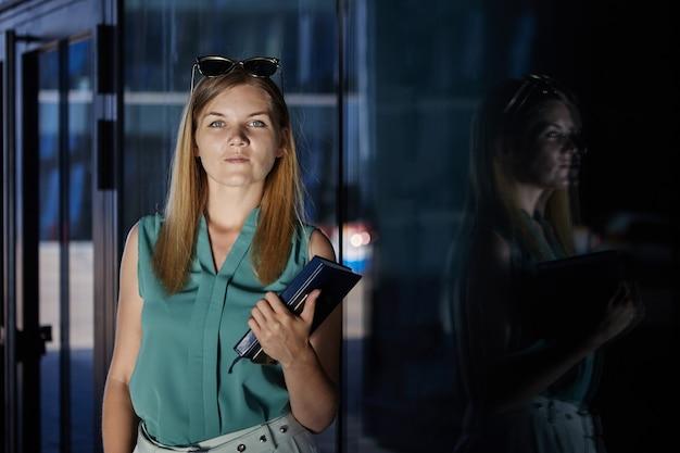 Задумчивая молодая красивая женщина с записной книжкой стоит в помещении