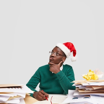 잠겨있는 젊은 흑인 산타 클로스는 턱을 잡고 명상 표현으로 위쪽으로 집중하고 축제 모자를 쓰고 있습니다.
