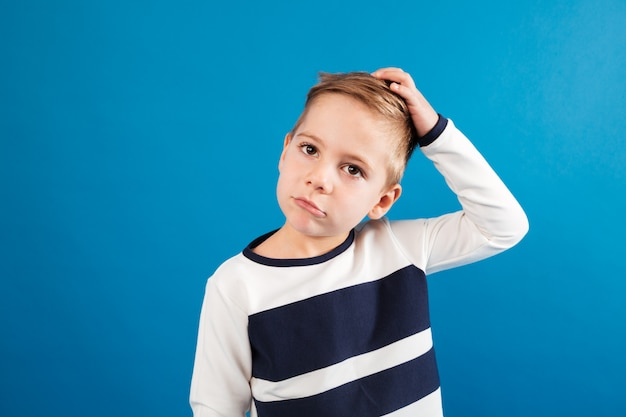 Pensive young boy in sweater touching his head