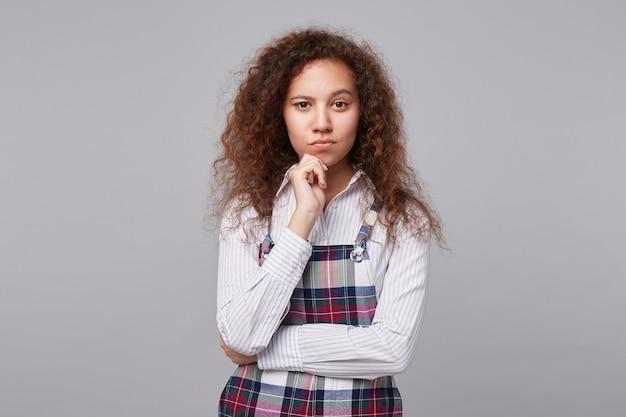 物思いにふける若い茶色の髪の巻き毛の女性は、上げられた手で彼女のあごを保持し、灰色でポーズをとって、驚くほど眉を上げます