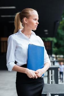 青いフォルダーを保持し、屋外を見て物思いにふける若いビジネス女性