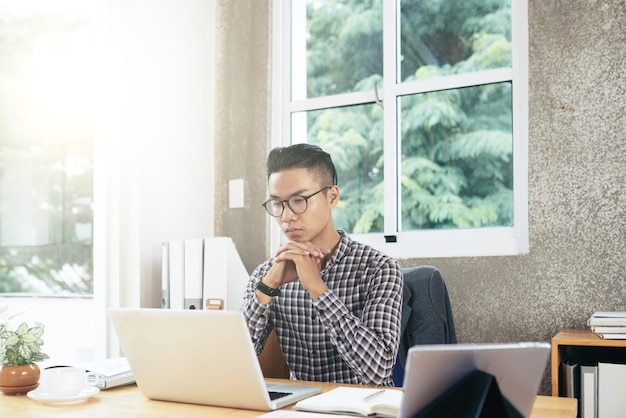 Pensive young businessman analyzing data in report on laptop screen