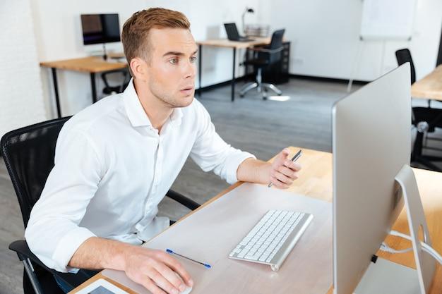 Задумчивый молодой бизнесмен сидит в офисе и работает с компьютером